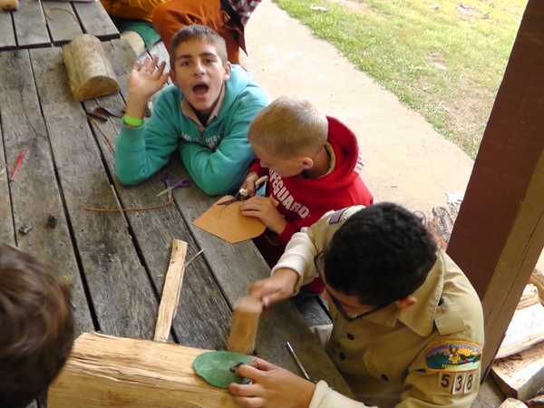Jacob_Harrison_and_Cristian_work_on_leatherworking_merit_badge.jpg